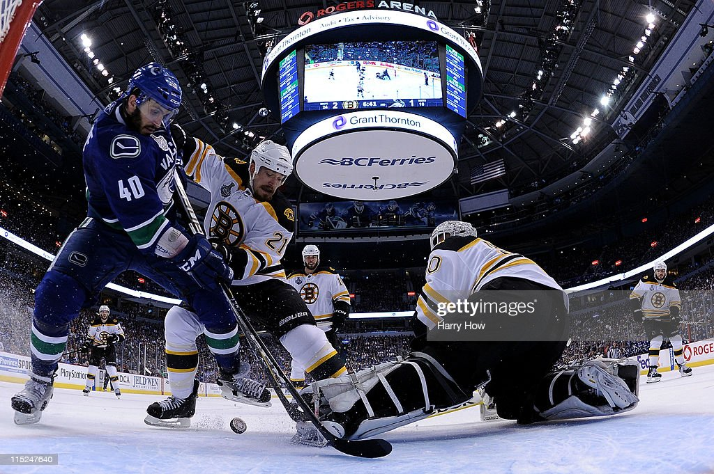 Maxim Lapierre of the Vancouver Canucks and Andrew Ference of the Boston Bruins fight for the puck in front of Tim Thomas of the Boston Bruins during...