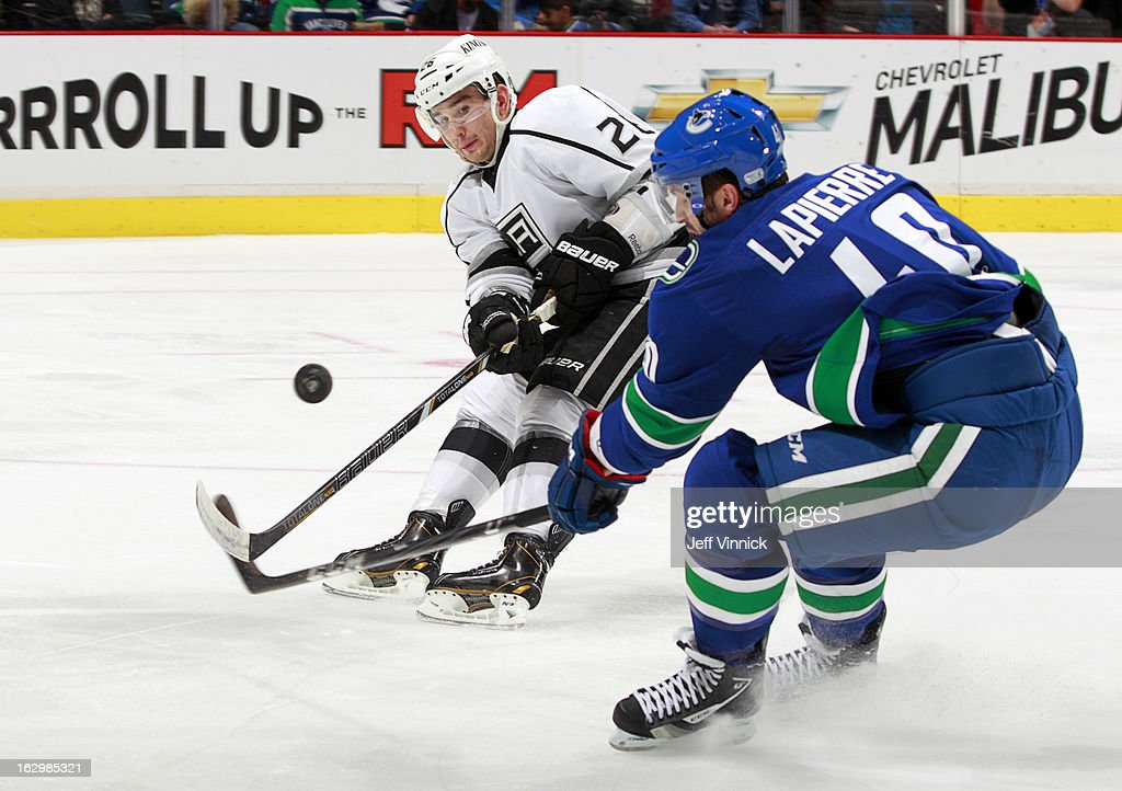 <a gi-track='captionPersonalityLinkClicked' href=/galleries/search?phrase=Maxim+Lapierre&family=editorial&specificpeople=718385 ng-click='$event.stopPropagation()'>Maxim Lapierre</a> #40 of the Vancouver Canucks and <a gi-track='captionPersonalityLinkClicked' href=/galleries/search?phrase=Slava+Voynov&family=editorial&specificpeople=8315719 ng-click='$event.stopPropagation()'>Slava Voynov</a> #26 of the Los Angeles Kings play the puck during their NHL game at Rogers Arena March 2, 2013 in Vancouver, British Columbia, Canada.