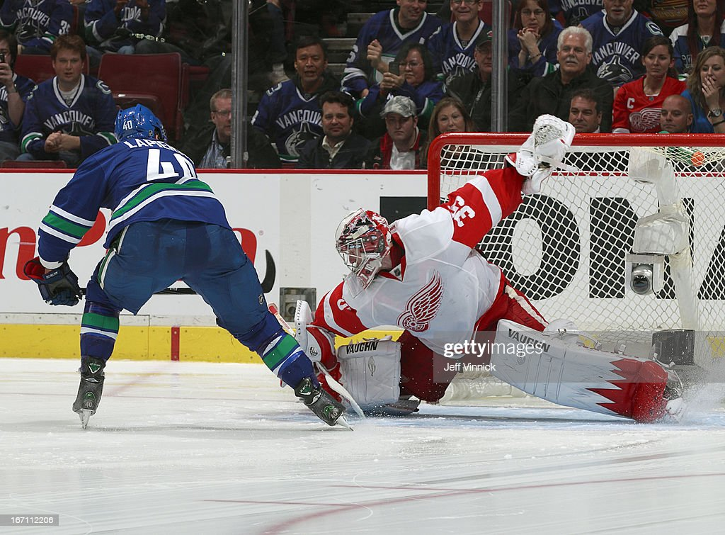 Maxim Lapierre of the Vancouver Canucks beats Jimmy Howard of the Detroit Red Wings for the shootout winning goal during their NHL game at Rogers...