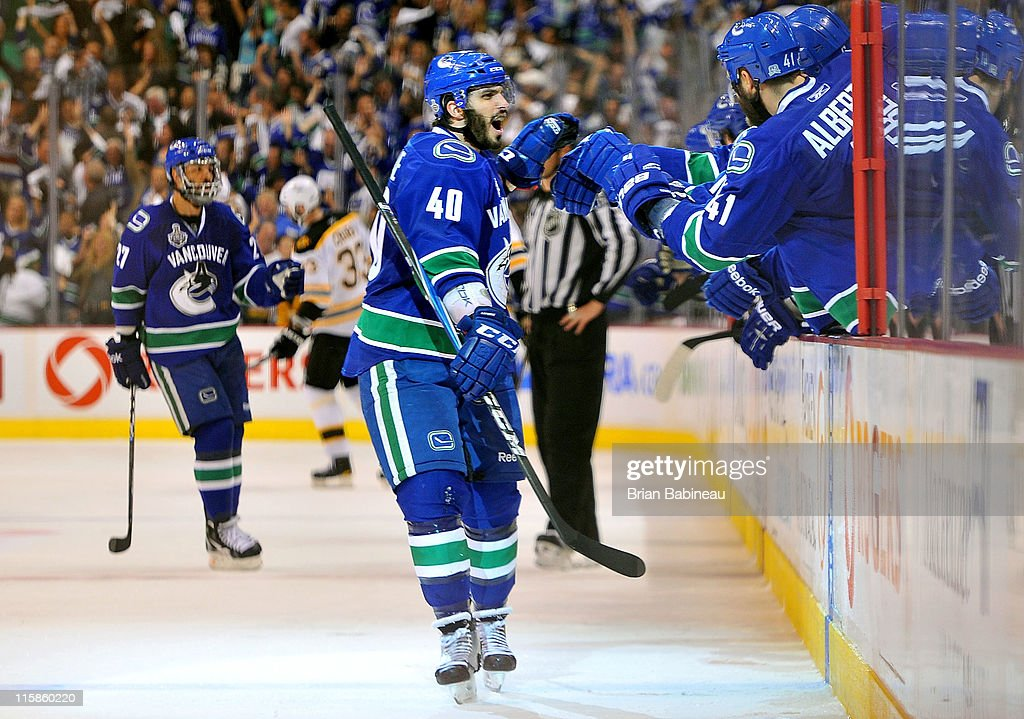 Maxim Lapierre of the Vancouver Canucks celebrates his third period goal with teammates during Game Five of the 2011 NHL Stanley Cup Finals at the...