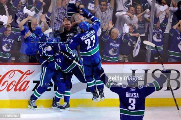 Maxim Lapierre of the Vancouver Canucks celebrates with Alexander Edler Manny Malhotra and Kevin Bieksa of the Vancouver Canucks after scoring a goal...