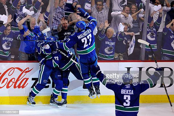 Maxim Lapierre of the Vancouver Canucks celebrates with Alexander Edler Manny Malhotra and Kevin Bieksa of the Vancouver Canucks after scoring a goal...