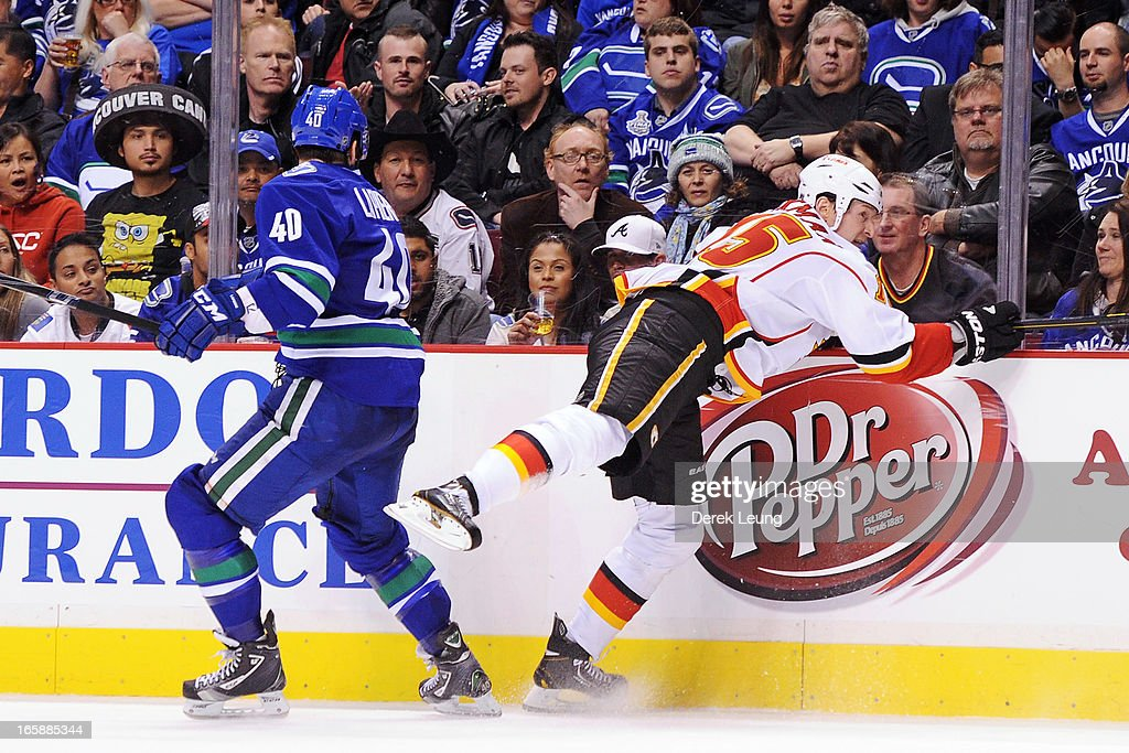 <a gi-track='captionPersonalityLinkClicked' href=/galleries/search?phrase=Maxim+Lapierre&family=editorial&specificpeople=718385 ng-click='$event.stopPropagation()'>Maxim Lapierre</a> #40 of the Vancouver Canucks collides with <a gi-track='captionPersonalityLinkClicked' href=/galleries/search?phrase=Tim+Jackman&family=editorial&specificpeople=2077074 ng-click='$event.stopPropagation()'>Tim Jackman</a> #15 of the Calgary Flames during an NHL game at Rogers Arena on April 6, 2013 in Vancouver, British Columbia, Canada.