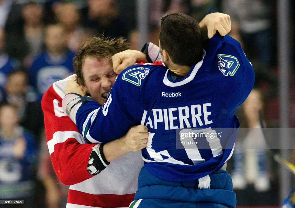 Maxim Lapierre of the Vancouver Canucks lands a punch on Justin Abdelkader of the Detroit Red Wings during fight in the second period in NHL action...