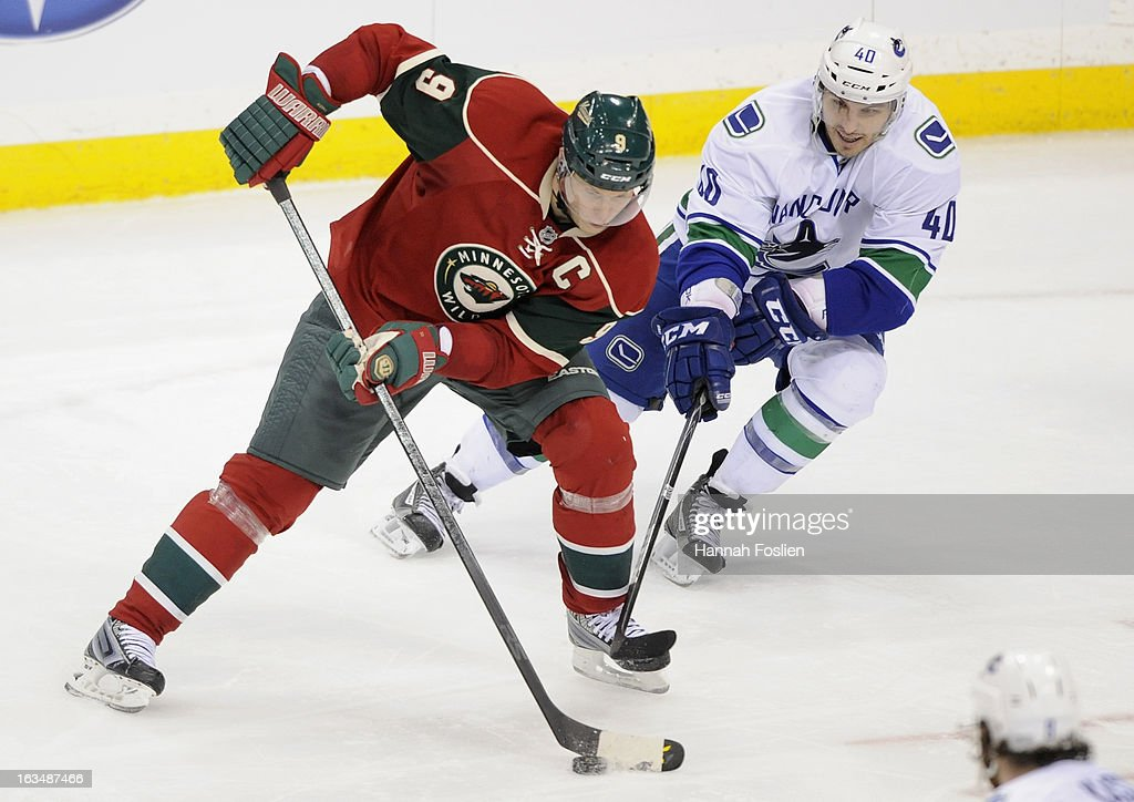<a gi-track='captionPersonalityLinkClicked' href=/galleries/search?phrase=Maxim+Lapierre&family=editorial&specificpeople=718385 ng-click='$event.stopPropagation()'>Maxim Lapierre</a> #40 of the Vancouver Canucks looks to take the puck away from <a gi-track='captionPersonalityLinkClicked' href=/galleries/search?phrase=Mikko+Koivu&family=editorial&specificpeople=584987 ng-click='$event.stopPropagation()'>Mikko Koivu</a> #9 of the Minnesota Wild during the third period of the game on March 10, 2013 at Xcel Energy Center in St Paul, Minnesota. The Wild defeated the Canucks 4-2.