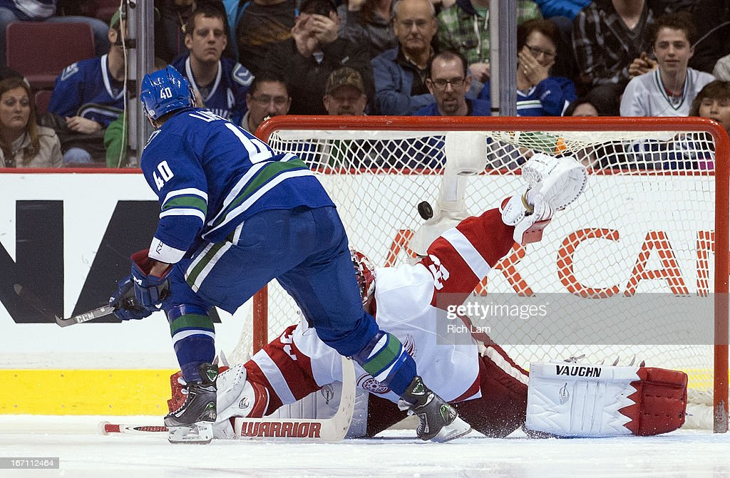 <a gi-track='captionPersonalityLinkClicked' href=/galleries/search?phrase=Maxim+Lapierre&family=editorial&specificpeople=718385 ng-click='$event.stopPropagation()'>Maxim Lapierre</a> #40 of the Vancouver Canucks scores on goalie <a gi-track='captionPersonalityLinkClicked' href=/galleries/search?phrase=Jimmy+Howard&family=editorial&specificpeople=2118637 ng-click='$event.stopPropagation()'>Jimmy Howard</a> #35 of the Detroit Red Wings during the shootout in NHL action on April 20, 2013 at Rogers Arena in Vancouver, British Columbia, Canada. The Canucks defeated the Red Wings 2-1.