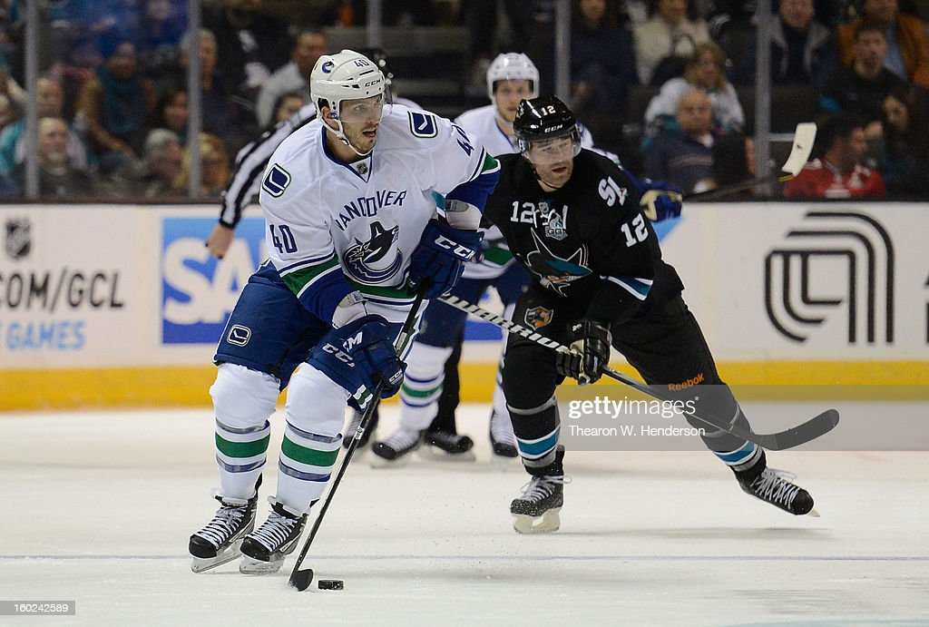 Maxim Lapierre #40 of the Vancouver Canucks skates with control of the puck chased by Patrick Marleau #12 of the San Jose Sharks at HP Pavilion on January 27, 2013 in San Jose, California.