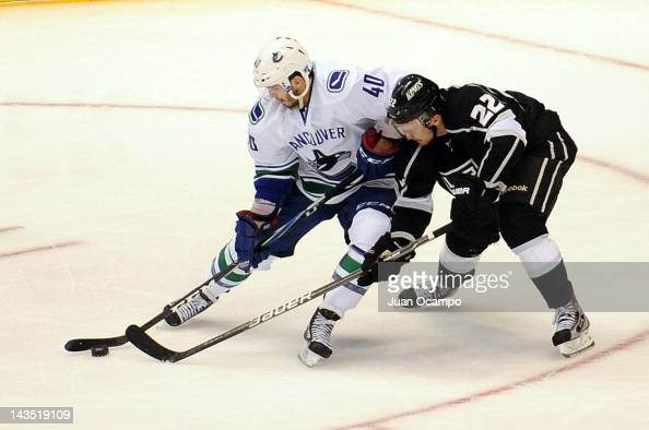 Maxim Lapierre of the Vancouver Canucks skates with the puck against Trevor Lewis of the Los Angeles Kings in Game Four of the Western Conference...