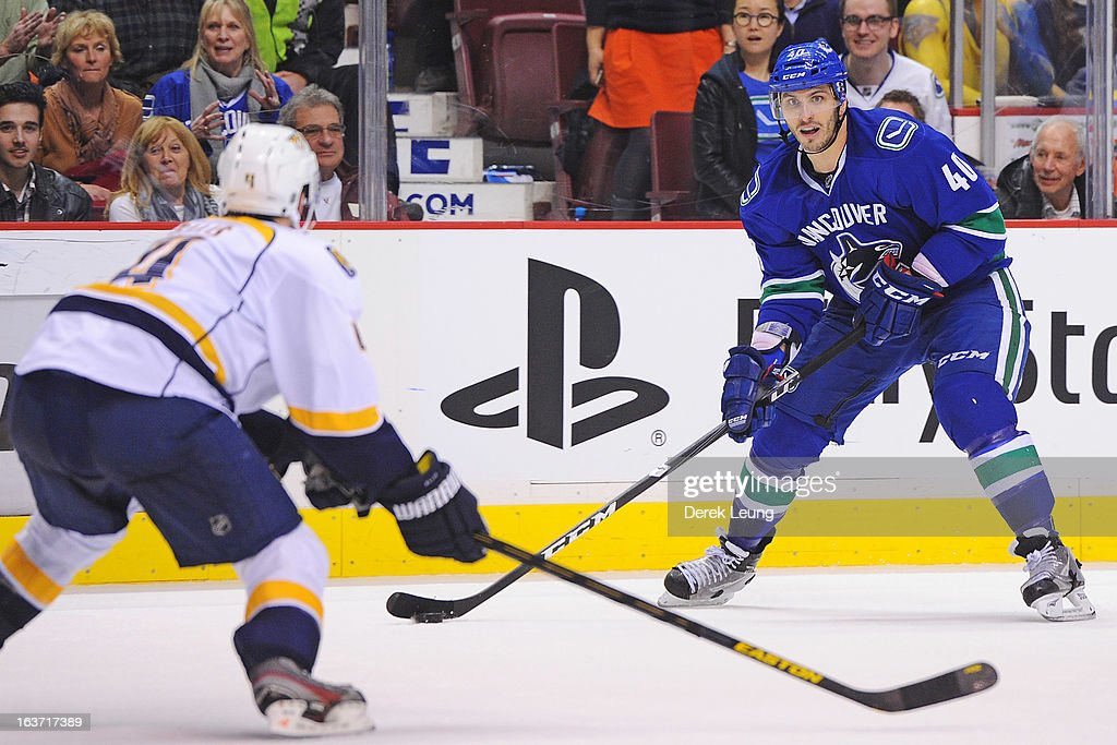 <a gi-track='captionPersonalityLinkClicked' href=/galleries/search?phrase=Maxim+Lapierre&family=editorial&specificpeople=718385 ng-click='$event.stopPropagation()'>Maxim Lapierre</a> #40 of the Vancouver Canucks skates with the puck against <a gi-track='captionPersonalityLinkClicked' href=/galleries/search?phrase=Ryan+Ellis&family=editorial&specificpeople=4616112 ng-click='$event.stopPropagation()'>Ryan Ellis</a> #4 of the Nashville Predators during an NHL game at Rogers Arena on March 14, 2013 in Vancouver, British Columbia, Canada. The Vancouver Canucks won 7-4.