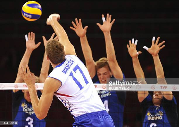 Maxim Mikhaylov of Russia spikes the ball over the net blocked by Finland`s Mikko Esko Pekka Olli Ojansivu and Toumas Sammelvou during their European...