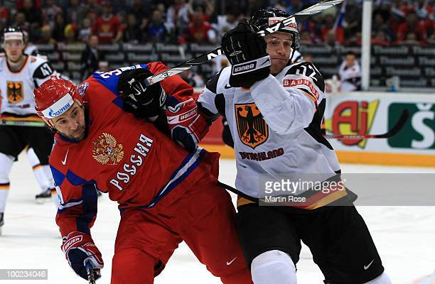 Maxim Sushinsky of Russia is blocked by Alexander Sulzer of Germany during the IIHF World Championship semifinal match between Russia and Germany at...