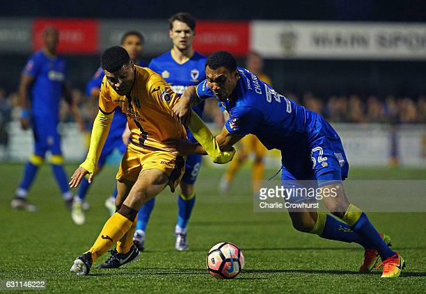 Maxime Biamou of Sutton United and Darius Charles of AFC Wimbledon compete for the ball during The Emirates FA Cup Third Round match between Sutton...