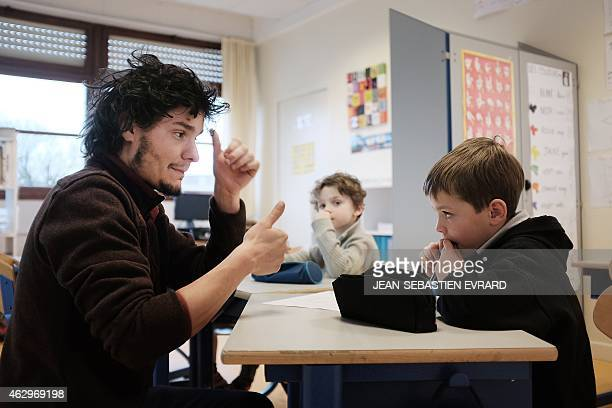 Maxime Bouhours a hearingimpaired teacher teaches sign language to hearingimpaired pupils at the Landry primary school of Rennes western France on...