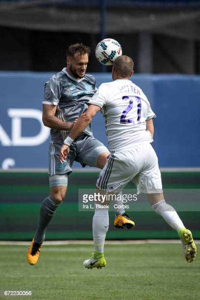 Maxime Chanot of New York City FC heads the ball to keep control against Scott Sutter of Orlando City SC during the MLS match between New York City...