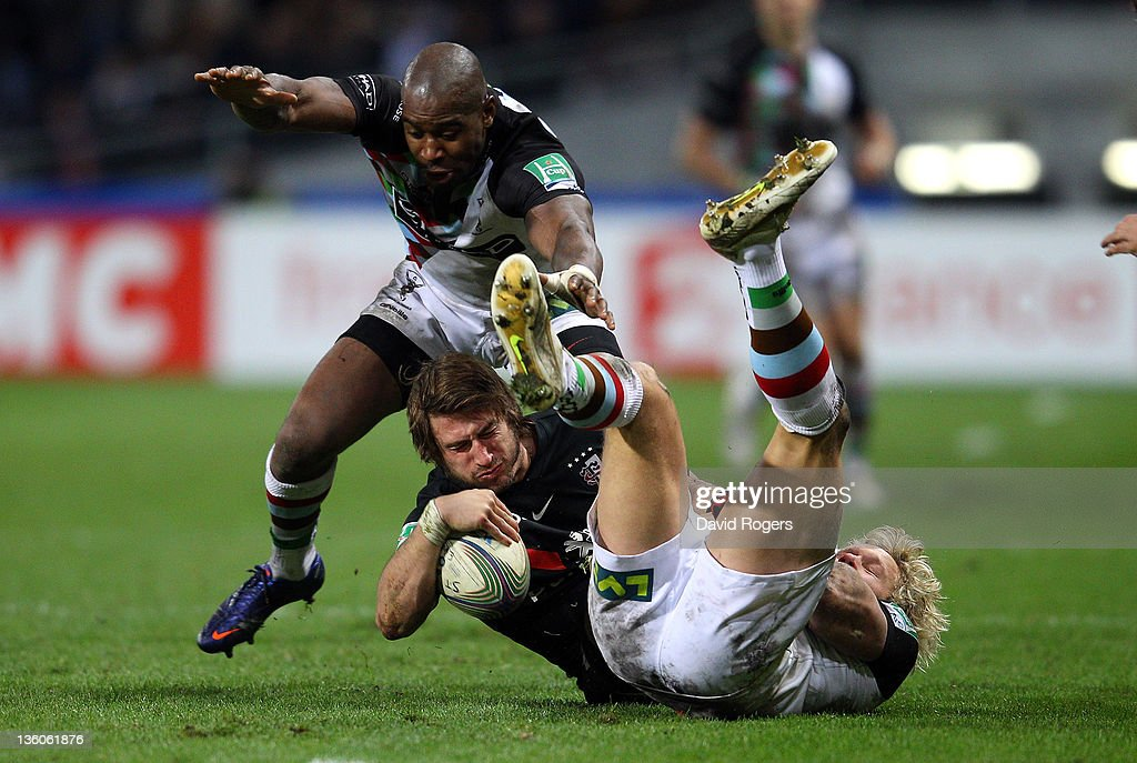 Maxime Medard of Toulouse is tackled by Ugo Monye (L) and Matt Hopper during the Heineken Cup match between Toulouse and Harlequins at Le Stadium on December 18, 2011 in Toulouse, .