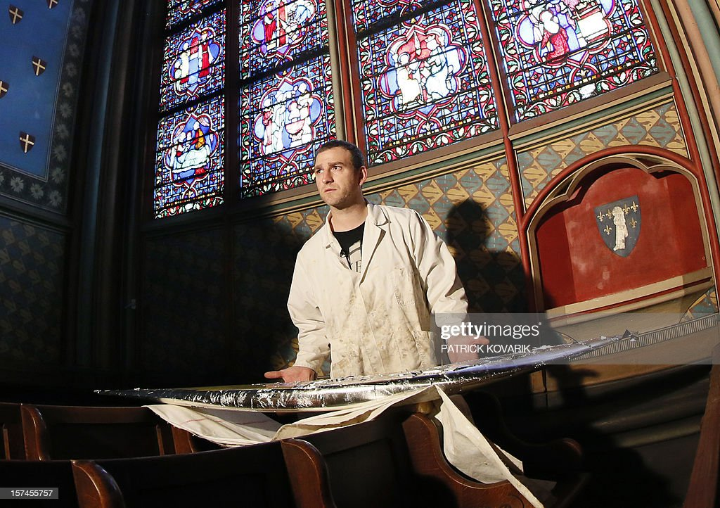 Maxime Seigneury, an artisan specialized in gold and silver plating, works on the restoration and white gold plating for a sacred object placed above the central cross inside the Notre-Dame de Paris cathedral in Paris on November 29, 2012. AFP PHOTO / PATRICK KOVARIK
