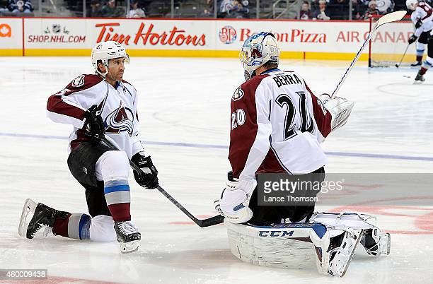 Maxime Talbot and goaltender Reto Berra of the Colorado Avalanche take part in the pregame warm up prior to NHL action against the Winnipeg Jets on...