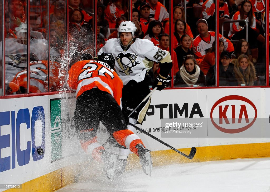 Maxime Talbot #25 of the Philadelphia Flyers crashes into the boards in front of Kris Letang #58 of the Pittsburgh Penguins at Wells Fargo Center on January 19, 2013 in Philadelphia, Pennsylvania.