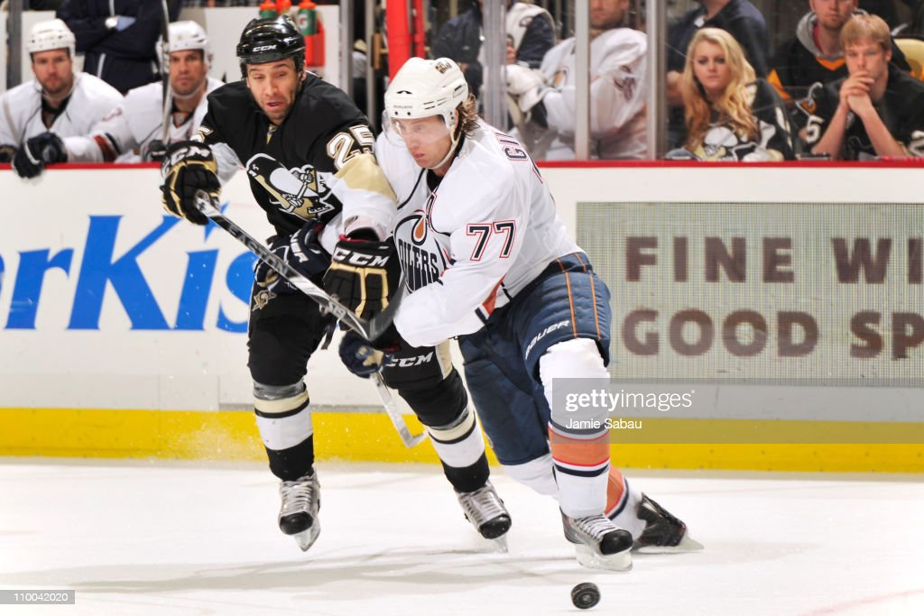 Maxime Talbot #25 of the Pittsburgh Penguins and Tom Gilbert #77 of the Edmonton Oilers battle for control of the puck on March 13, 2011 at CONSOL Energy Center in Pittsburgh, Pennsylvania.