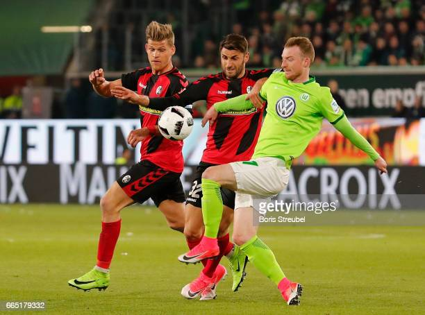 Maximilian Arnold of VfL Wolfsburg battles for the ball with Vincenzo Grifo and Florian Niederlechner of Freiburg during the Bundesliga match between...