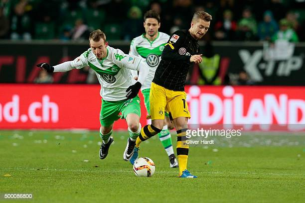 Maximilian Arnold of Wolfsburg and Marco Reus of Dortmund compete for the ball during the First Bundesliga match at between VfL Wolfsburg and...