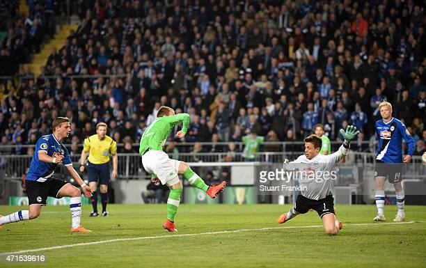 Maximilian Arnold of Wolfsburg scores his team's fourth goal past goalkeeper Alexander Schwolow of Bielefeld during the DFB Cup Semi Final match...