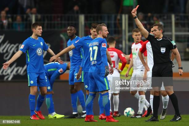 Maximilian Arnold of Wolfsburg sees a red card by referee Tobias Stieler during the Bundesliga match between FC Augsburg and VfL Wolfsburg at...