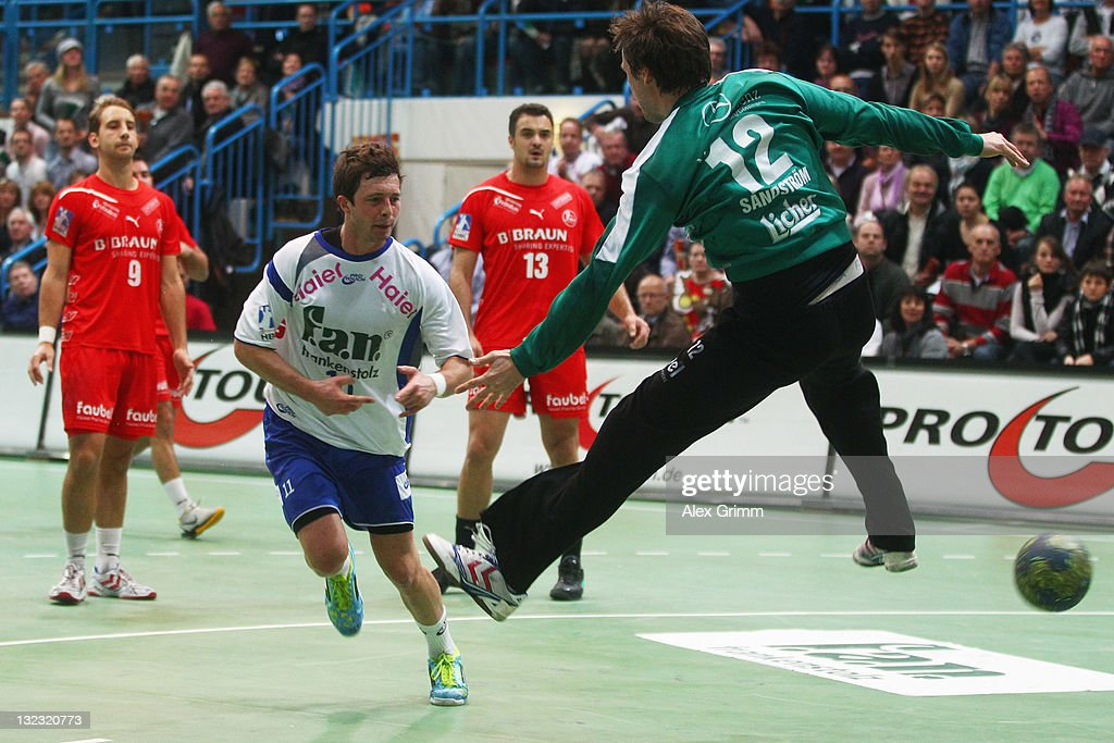 Maximilian Holst of Grosswallstadt scores agoal against goalkeeper <a gi-track='captionPersonalityLinkClicked' href=/galleries/search?phrase=Per+Sandstroem&family=editorial&specificpeople=2704493 ng-click='$event.stopPropagation()'>Per Sandstroem</a> of Melsungen during the Toyota Handball Bundesliga match between T VGrosswallstadt and MT Melsungen at f.a.n. frankenstolz arena on November 11, 2011 in Aschaffenburg, Germany.