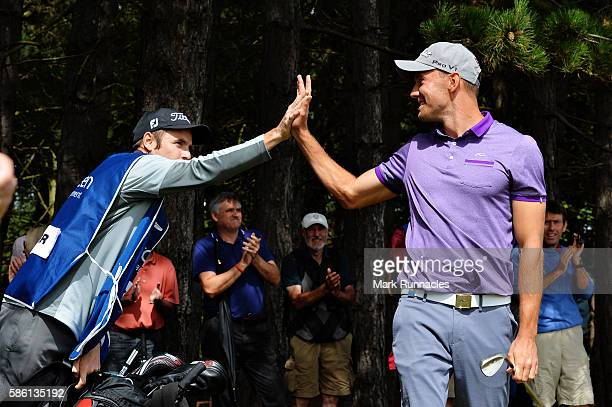 Maximilian Kieffer of Germany gets a high five from his caddy after chipping in on hole 18 after winning his match on day two of the Aberdeen Asset...