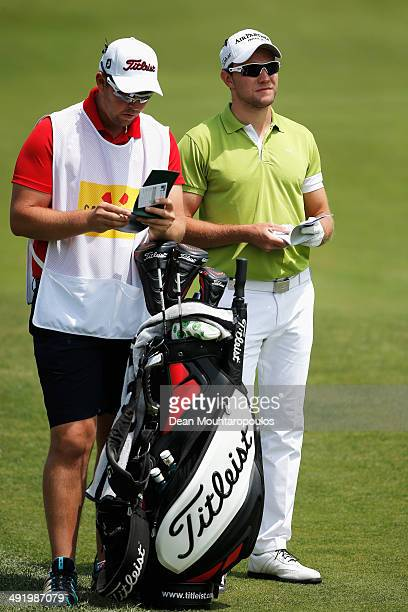 Maximilian Kieffer of Germany speaks to his caddie before he hits his second shot on the 1st hole during the final round of the Open de Espana held...