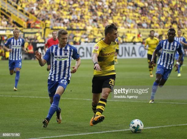 Maximilian Philipp of Borussia Dortmund challenges with Mitchell Weiser of Hertha BSC Berlin during the Bundesliga soccer match between Borussia...