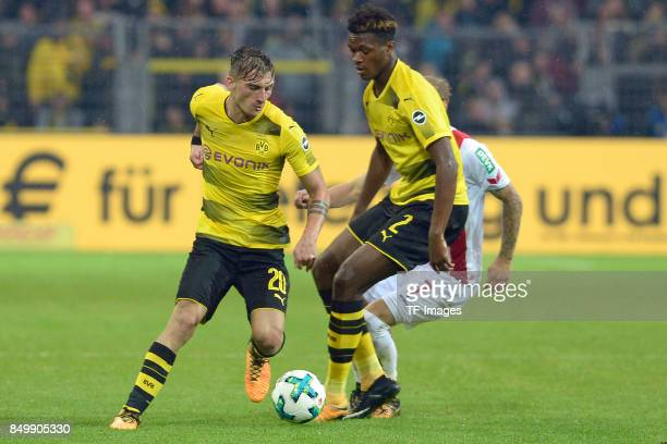 Maximilian Philipp of Dortmund and DanAxel Zagadou of Dortmund and Marcel Risse of Koeln battle for the ball during the Bundesliga match between...