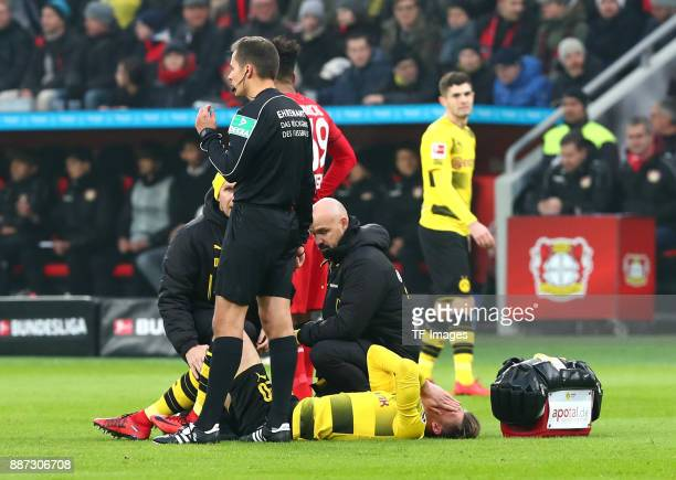Maximilian Philipp of Dortmund receives medical help from Thomas Zetzmann of Dortmund and Dr Markus Braun of Dortmund during the Bundesliga match...