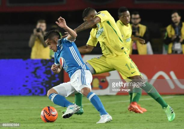 Maximiliano Nuñez of Millonarios fights for the ball with Elkin Blanco of Atletico Nacional during the Semi Finals first leg match between...