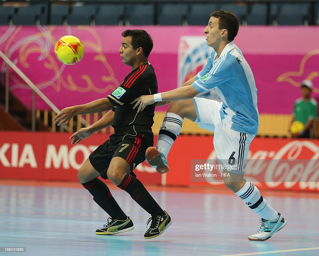 Maximiliano Rescia of Argentina tries to tackle Jorge Rodriguez of Mexico during the FIFA Futsal World Cup Thailand 2012 Group D match between...