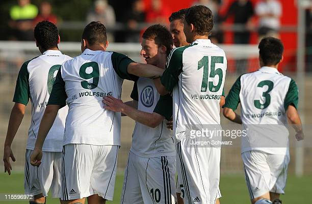 Maximillian Arnold of Wolfsburg is hugged by teammates after scoring during the A Junior Championships semifinal first leg match between Bayer...