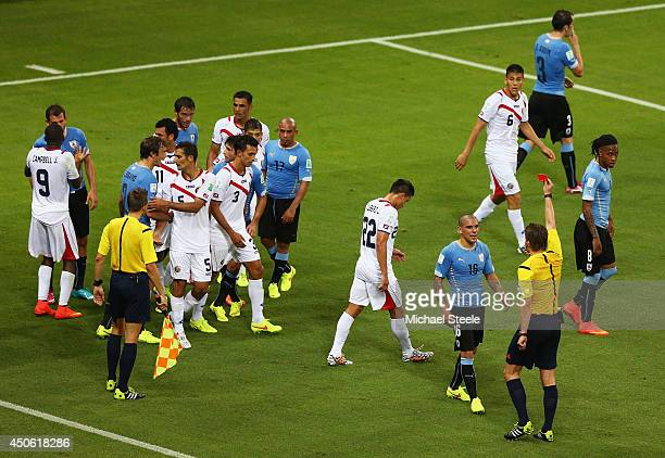 Maximilliano Pereira of Uruguay is shown a red card by referee Felix Brych after a foul on Joel Campbell of Costa Rica during the 2014 FIFA World Cup...
