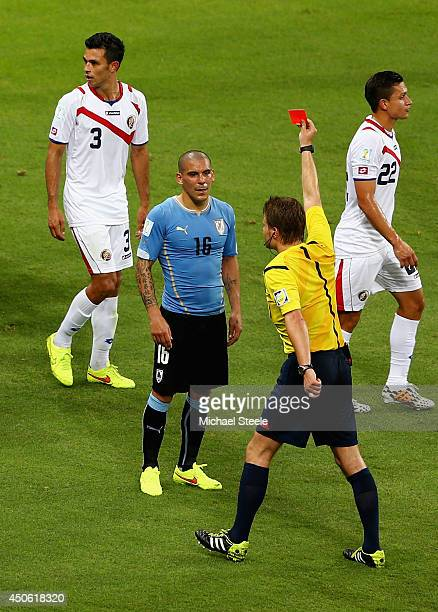 Maximilliano Pereira of Uruguay is shown a red card by referee Felix Brych after a foul during the 2014 FIFA World Cup Brazil Group D match between...