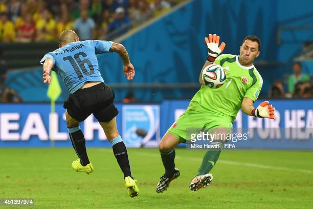 Maximilliano Pereira of Uruguay shoots while David Ospina of Colombia makes a save during the 2014 FIFA World Cup Brazil Round of 16 match between...