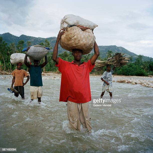 Maxo Santus pauses to face the camera for a moment while he tries to earn a little money working as an informal porter helping people cross the river...