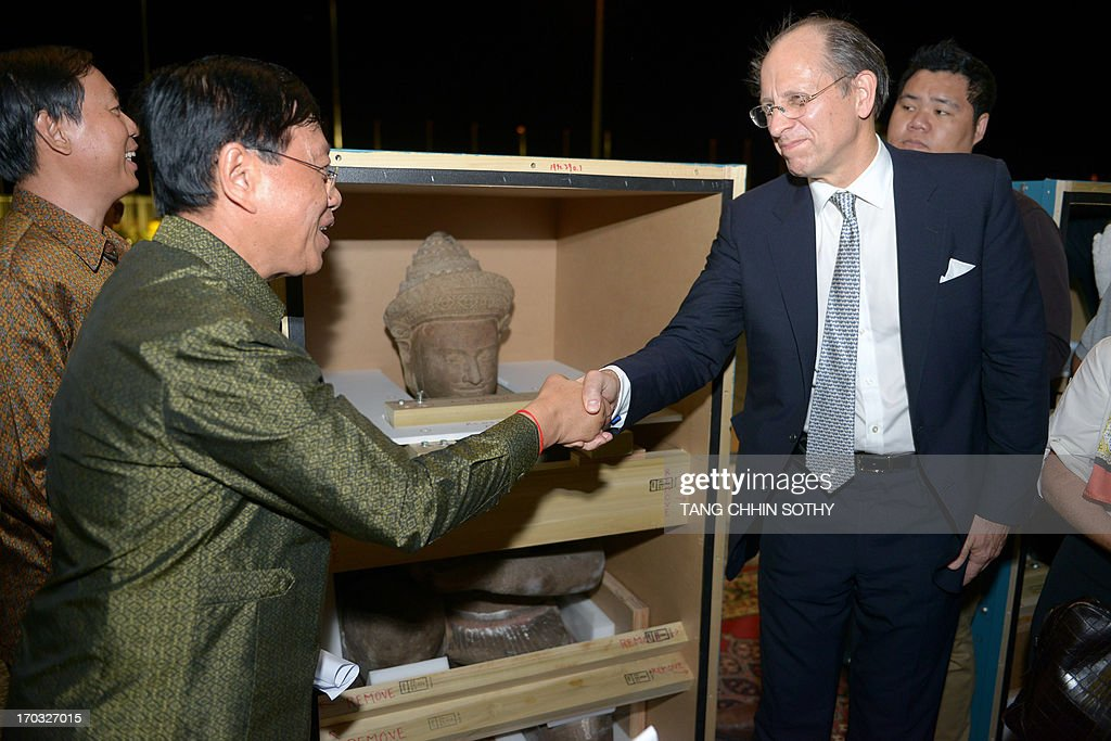 Maxwell Hearn (R), Douglas Dillon Chairman Department of Asian Art at the Metropolitan Museum of Art in New York, shakes hands with Chan Tani (2nd-L), Cambodian secretary of state of the office of the council of ministers, in front of a 10th century statue at Phnom Penh International Airport on June 11, 2013. Two 10th century statues that Cambodia says were looted from a jungle temple several decades ago were returned home on June 11 from the New York museum in what the kingdom described as a 'historic' moment.