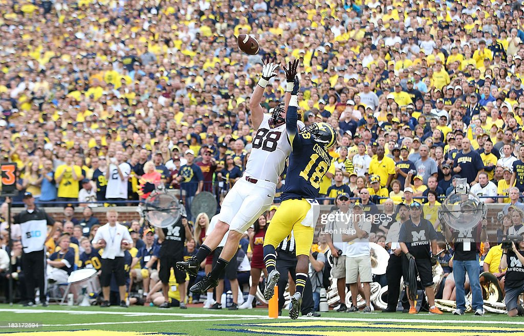 Maxx Williams of the Minnesota Golden Gophers makes the catch over Blake Countess of the Michigan Wolverines for a first quarter touchdown during the...