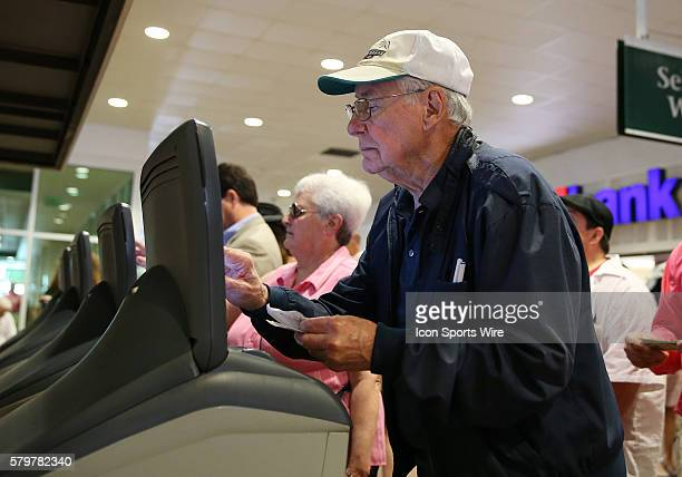 This racing fan places a bet at an automated wager machine before the 141st running of the Kentucky Oaks at Churchill Downs in Louisville Ky