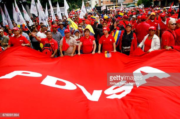 CARACAS May 1 2017 Venezuelan oil sector workers and government supporters hold a banner of Petroleum of Venezuela during a march to commemorate the...