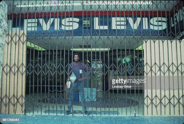LOS ANGELES May 1 Rodney King Riot View of a man standing protectively behind grate at entrance of business that was left untouched on Hollywood...