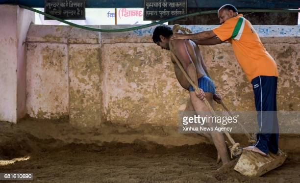 NEW DELHI May 10 2017 A Pehlwani wrestler levels the mud ground as part of the strength training in Guru Hanuman Akhara training center in New Delhi...