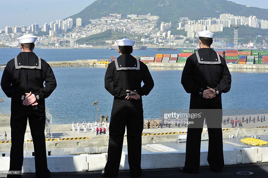 May 11, 2013 - Sailors man the rails as the aircraft carrier USS Nimitz (CVN-68) pulls in to Busan, Republic of Korea, for a port visit.
