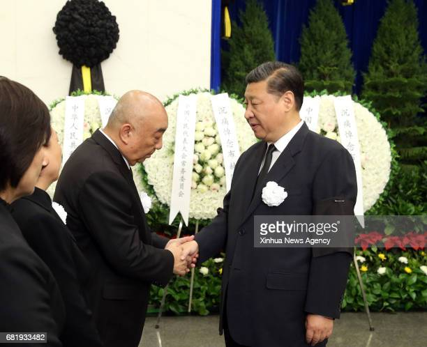 Chinese President Xi Jinping shakes hands with a family member of Buhe a former vice chairman of the Standing Committee of the National People's...