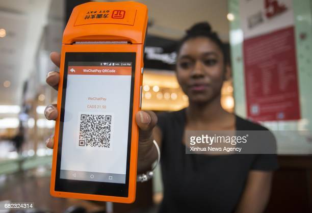 A staff member shows a WeChat Pay QR code at Yorkdale Shopping Centre in Toronto Canada May 11 2017 Canada's shopping mall Yorkdale Shopping Centre...