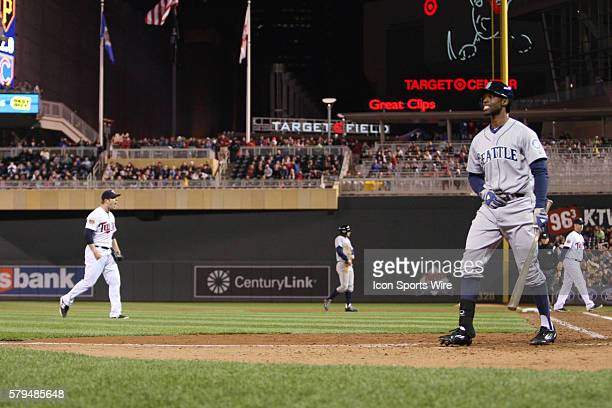 May 16 2014 Minnesota Twins pitcher Casey Fien celebrates in the background as Seattle Mariners outfielders James Jones walks off after striking out...